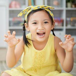 Sweet little Vietnamese girl making scary face